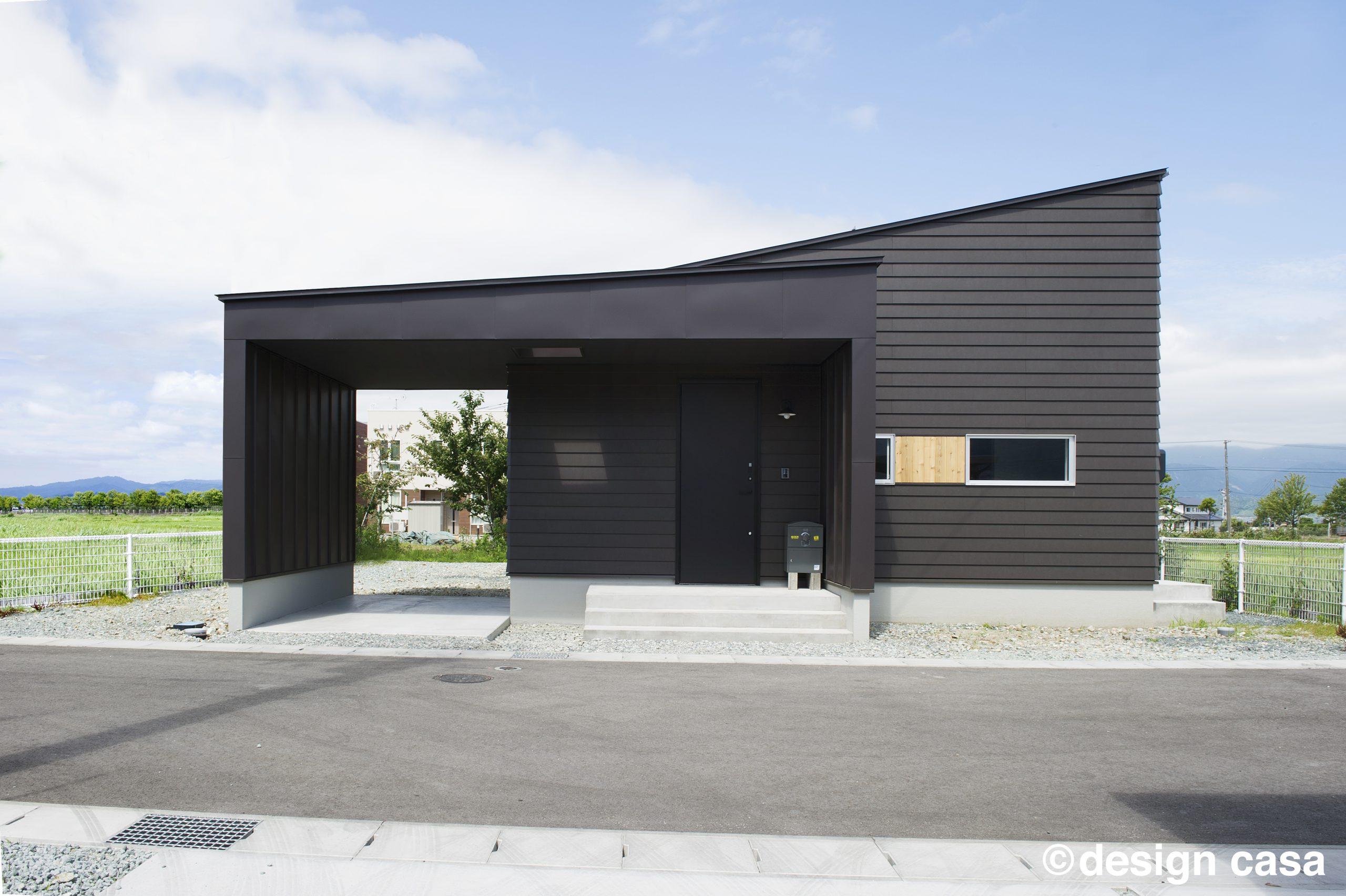 平屋のガレージハウスの外観 黒の金属サイディングとシンプルな平屋のシルエットがかっこいい
