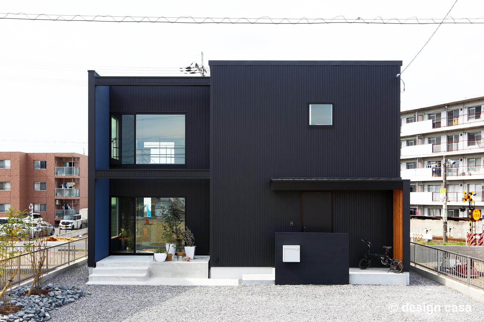 大きな窓の面に袖壁を出したキューブ型の家